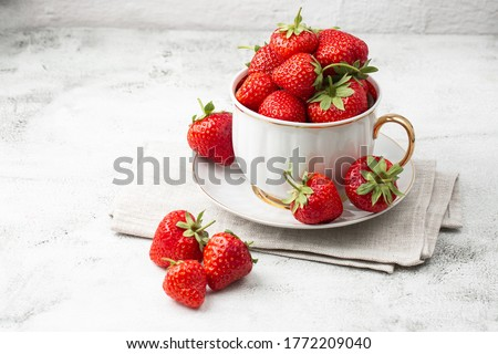 Fresh strawberries in a white cup on marble white table. Fresh nice strawberries. Strawberry field on fruit farm. Heap of Red strewberry on plate. Juice strawberry. Strawberry field on fruit farm.