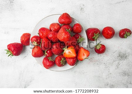 Fresh strawberries in plate on marble white table. Fresh nice strawberries. Strawberry field on fruit farm. Heap of Red strewberry on plate close up. Juice strawberry. Strawberry field on fruit farm.