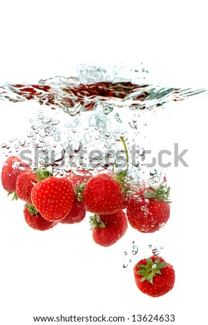 fresh strawberries splashing into water