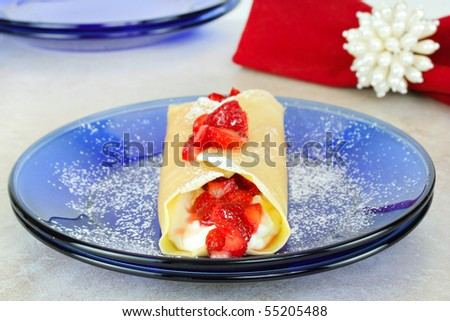 Fresh strawberries with crepes or pancakes and sugar.  Selective focus on end of crepe.