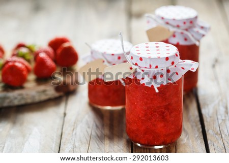 Fresh strawberry homemade jam in jar on wood background. healthy organic and vegan food.