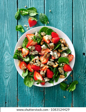 Fresh strawberry salad with spinach leaves, blue cheese and walnuts.