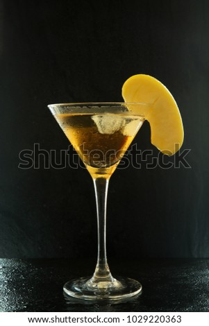 Fresh summer appletini cocktail in a martini glass with an apple slice on a black textured surface with water drops and reflections #1029220363