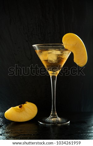 Fresh summer appletini cocktail in a martini glass with an apple slices on a black, wet textured surface with water drops and reflections #1034261959