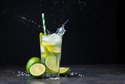 fresh summer caipirinha cocktail with splash on a black background. green fruit lime on table