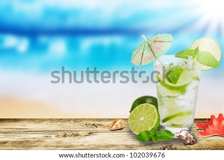Fresh summer cocktail on wooden table. Blur beach on background