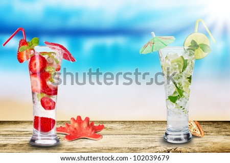 Fresh summer cocktails on wooden table. Blur beach on background