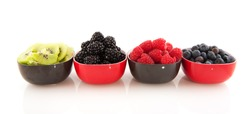 Fresh summer fruit in little bowls isolated over white