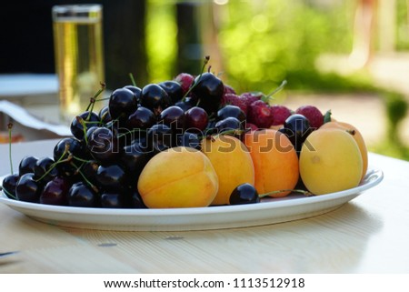 Fresh summer fruits on a white plate. Cherries and apricots and strawberries on a white plate at a picnic. Summer healthy food snack.  #1113512918