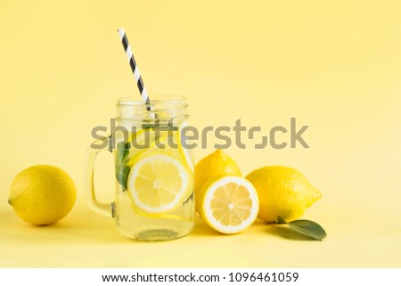 Fresh summer fruits water or lemonade with lemon, orange and mint on yellow background. Close up.