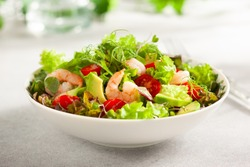 Fresh summer salad with shrimp, avocado and tomato cherry in bowl on light table. Concept of healthy eating.