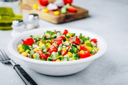 Fresh summer sweet corn salad bowl with tomatoes, cucumbers, red onions and parsley.