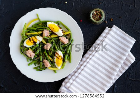 Fresh summer warm salad with cooked green beans, tuna, boiled eggs and sauce balsamico glassa in white plate on black stone background. Healthy eating concept. Top view.