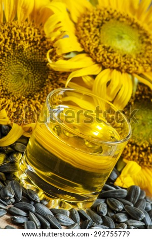 Fresh sunflower oil in a glass with flowers sunflowers and sunflower seeds, selective focus