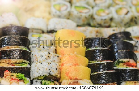 Fresh sushi rolls with salmon, avocado, tuna and cucumber. Maki plate with rice and nori. Delicious Japanese food with sushi roll in close up picture. Healthy kale and sushis. Holiday food dish.