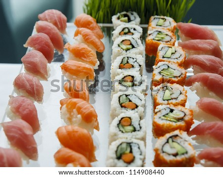 Fresh sushi, sushimi and california rolls on a glass tray