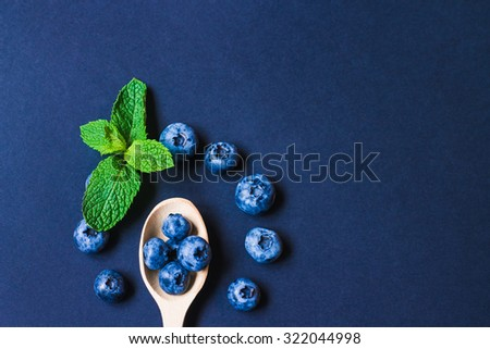 Fresh sweet blueberry fruit and leaf of mint.. Dessert healthy food. Group of ripe blue juicy organic berries. Raw summer diet. Delicious nature vegetarian ingredient. Black background.