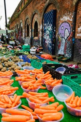 Fresh sweet carrots, potatoes, broccoli at Brick Lane market. Old building with graffities at backgrounds. London, UK.