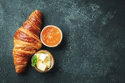 Fresh sweet croissant with butter and orange jam for breakfast. Continental breakfast on a black concrete table. Top view with copy space. Flat lay