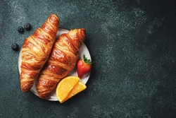 Fresh sweet croissants with butter and orange jam for breakfast. Continental breakfast on a black concrete table. Top view with copy space. Flat lay.