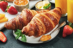 Fresh sweet croissants with butter and orange jam for breakfast. Continental breakfast on a black concrete table.