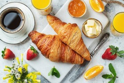 Fresh sweet croissants with butter and orange jam for breakfast. Continental breakfast on a white concrete table. Top view. Flat lay.