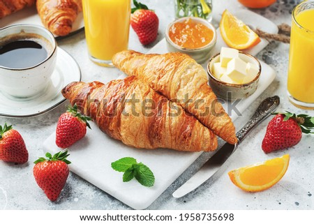 Fresh sweet croissants with butter and orange jam for breakfast. Continental breakfast on a white concrete table. Photo stock ©