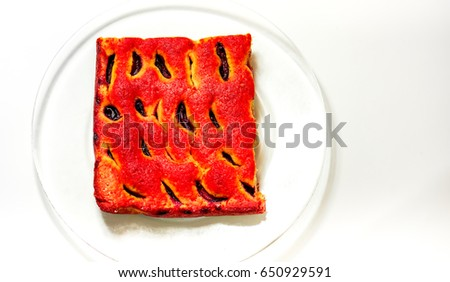Fresh sweet homemade cake with plumps and texture-baked dough cut into square against clear glass plate. Peace of home holiday cake as best addition to a cup of coffee or tea