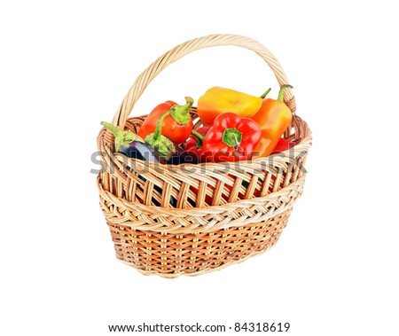 Fresh sweet red pepper and eggplant in a wattled basket on white