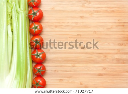 Fresh sweet tomatoes and celery on a cutting board