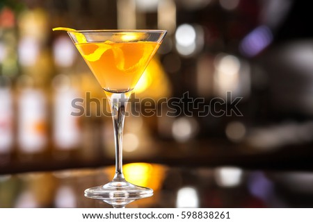 Fresh tall glass of tropical cocktail with rum and orange juice at bar counter background.