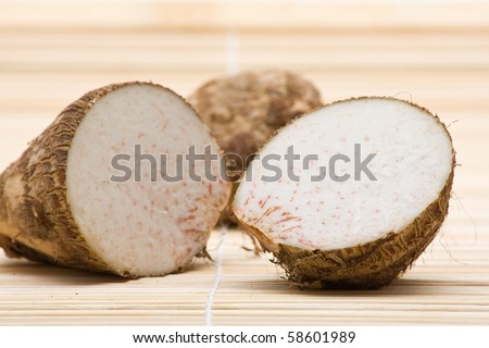 Fresh taro root cut in half on bamboo mat