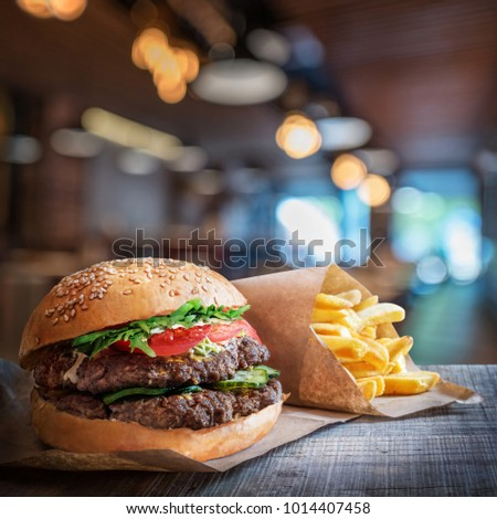 Fresh tasty burger and french fries on wooden table. Hamburger fast food restaurants background.