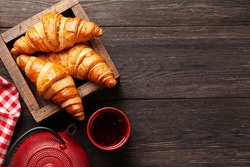 Fresh tasty croissants and tea. Breakfast meal. Top view flat lay with copy space