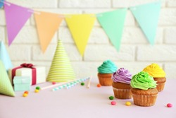 Fresh tasty cupcakes and birthday decor on blurred background