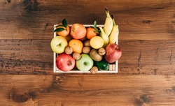 Fresh tasty fruit in a crate and wooden table top view, healthy food concept