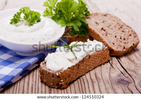 fresh tasty herbal creme cheese and bread on wooden table