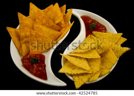Fresh tasty nachos served on a white shaped plate on a black background