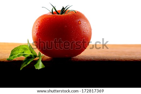 fresh tasty tomato with aromatic basil leaf on wooden board