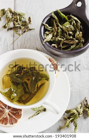 fresh tea from the leaves of mint on a table- health and diet concept