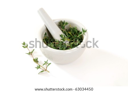 Fresh thyme in a mortar with a pestle waiting to be ground