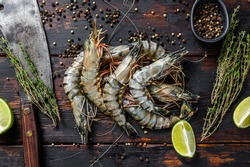 Fresh tiger shrimps, prawns with spices and herbs. Black woodenbackground. Top view