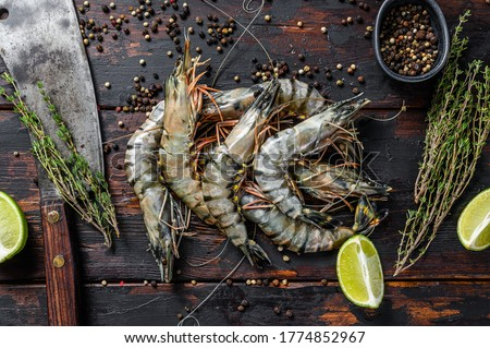 Fresh tiger shrimps, prawns with spices and herbs. Black woodenbackground. Top view Stockfoto ©