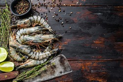 Fresh tiger shrimps, prawns with spices and herbs. Black woodenbackground. Top view. Copy space