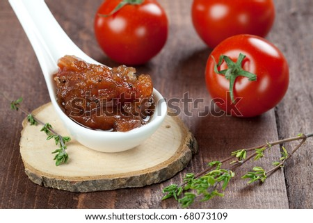 fresh tomato chutney on spoon with thyme
