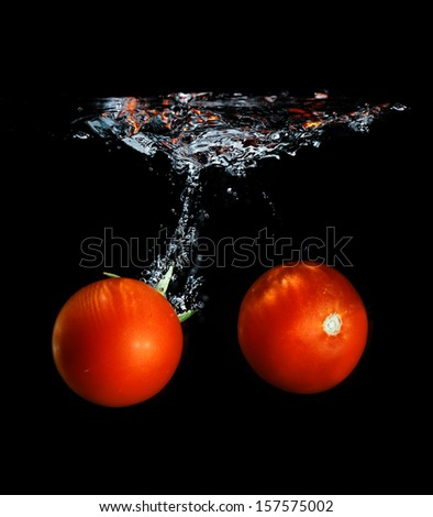 Fresh tomato dropped into water, isolated on dark background