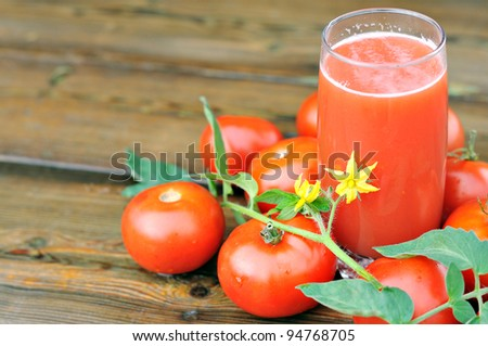 Fresh tomato juice and tomato on a wooden table.