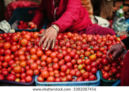 Fresh tomato on street asian market. Red coloured vegetable and seller clothes