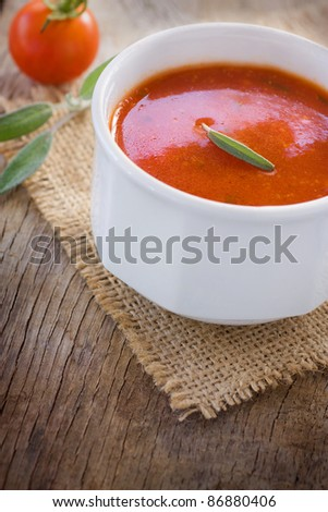 Fresh tomato soup with cherry tomatoes and fresh herbs and copyspace