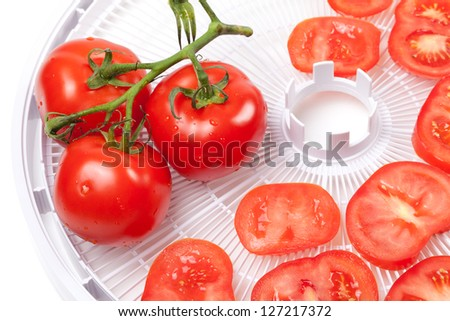 Fresh tomato with water drops on food dehydrator tray